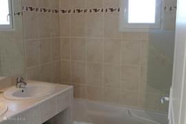 Badkamer met ligbad en dubbel wastafelmeubel