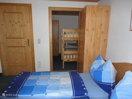 In the third small bedroom has a bunk bed, with a small wardrobe. This room has an open door to bedroom 2
