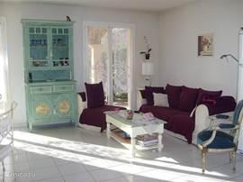 Lichte woonkamer met 2 x 2 openslaande deuren naar de tuin (zuid)