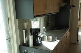 Ruime keuken met grote koel-vries combinatie, magnetron, oven, koffiezetapparaat en broodrooster