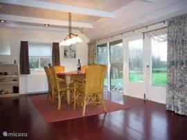 Ruime woon- eetkamer met openslaande deuren naar een terras.