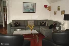 Een comfortabele en sfeervolle zitkamer, met voldoende zitplaatsen en eveneens met uitzicht op de tuin.