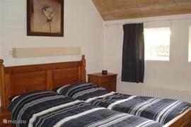 De ruime, maar toch knusse slaapkamer op de begane grond met een comfortabel tweepersoons bed en een linnenkast.