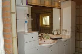 De badkamer is voorzien van modern sanitair, een dubbele wastafel en een aparte doucheruimte.