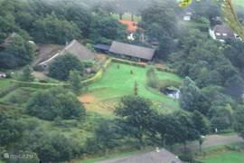 De luchtfoto geeft een beeld van het perceel van het voormalige Saksische boerenerf, dat nu geheel  omzoomd is met bosachtige begroeiing.
