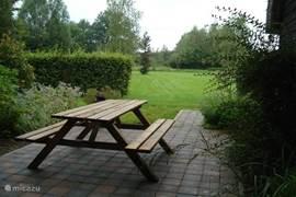 Het terras met picknicktafel biedt uitzicht op de aangrenzende tuin met vijver. Dit terras is gericht op het zuiden.