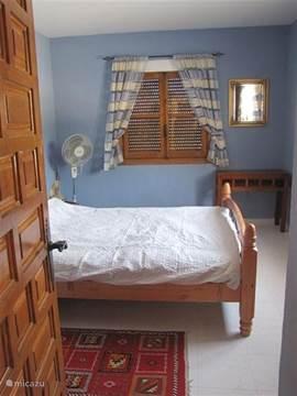De blauwe slaapkamer met een tweepersoonsbed, een hang- en een legkast. Deze slaapkamer heeft uitzicht op de tuin