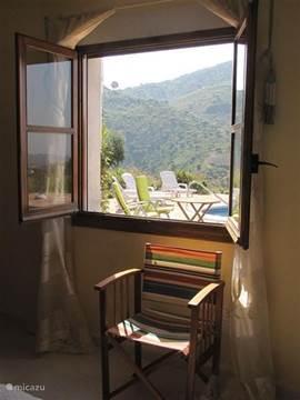 De ruime en lichte slaapkamer met uitzicht op het zwembad en de terrassen