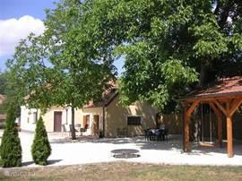 achterzijde van het huis in de zomer. Een heerlijke grote notenboom voor schaduw en een carport voor de auto