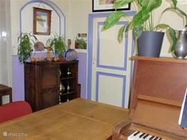 Als u het huis binnenkomt vindt u de bibliotheek waar naast de boekenkasten o.a. een bureau en piano staan.