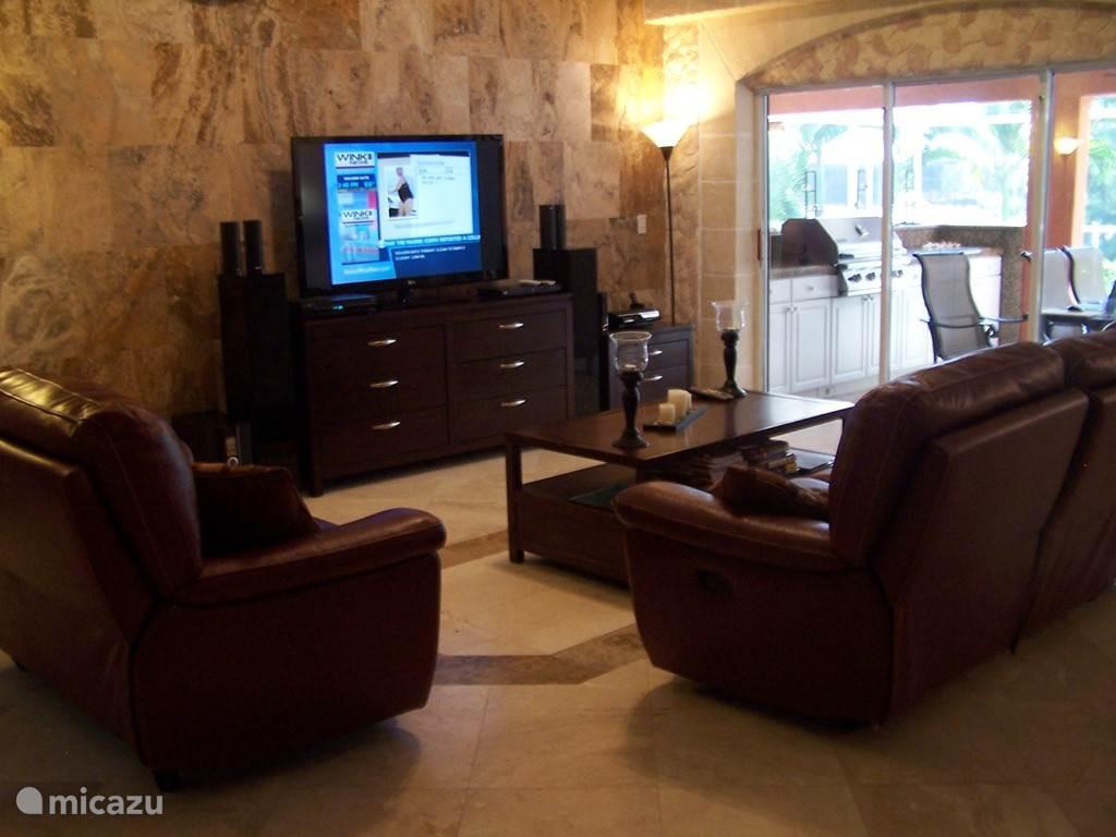 Links ziet u de woonkamer met drie tweepersoons banken, een groot dressoir en een flatscreen tv met playstation3 en blue ray. Schuif de deuren open en er is een directe toegang tot de buitenkeuken en het zwembad.