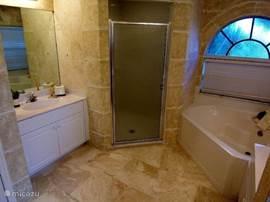 De masterbathroom is vanuit de masterbedroom te bereiken. Een ruime badkamer met twee wastafels, een inloopdouche, toilet en ruim ligbad. Zoals in heel de villa zijn de vloeren van natuursteen en de wanden natuursteen/marmer. Alles koel en hygiënisch.