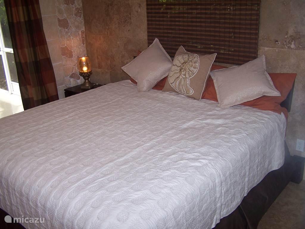 Slaapkamer 2 ( de schelpenkamer) Gelegen aan het zwembad, heeft openslaande deuren. Grote kledingkast en dressoir met tv. Het bed is kingsize.