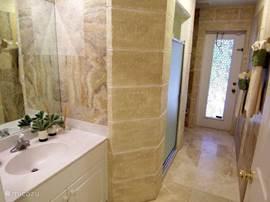 De tweede badkamer is heel practisch. Gasten van de 2 slaapkamers kunnen gebruik maken van deze badkamer die voorzien is van een ruime wastafel, toilet en inloopdouche. Daarnaast heeft deze badkamer 2 ruime kasten en toegang tot het terras en het zwembad.