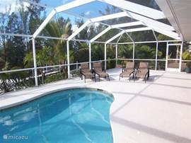 Overdag schijnt de zon. Vier luxe zonnebedden bij het zwembed. Puur genieten aan de rand van uw privé zwembad.