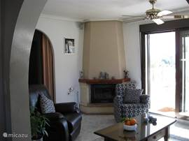 zitkamer met openhaard met leerbankje relexstoel en kuipstoel met flatscreen tv Ned. zenders