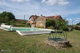 Zicht op het huis en de tuin met op de voorgrond het zwembad met infinity en historische waterput.