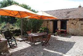 De eettafel onder de parasols buiten op de binnenplaats.