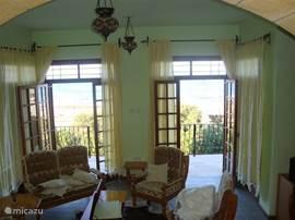 De woonkamer heeft grote open slaande deuren waardoor de zee uw huiskamer inkomt.