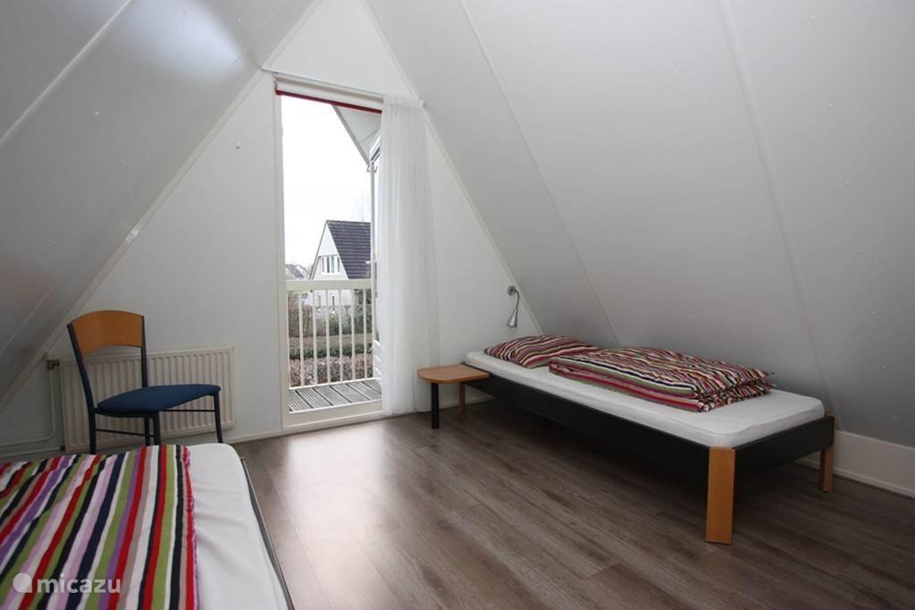 Eén van de 2 slaapkamers boven, in dit geval met een klein balkon op het zuiden
