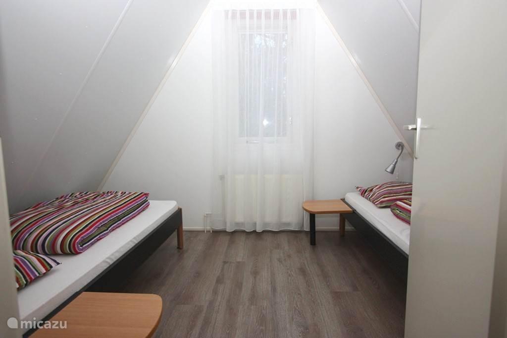 De 2e slaapkamer boven, uitkijkend op de bosrand