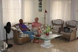 de woonkamer beschikt over een comfortabele loungeset, licht en koel