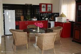 keuken met eettafel en 6 rotanstoelen die met de zithoek één geheel vormen