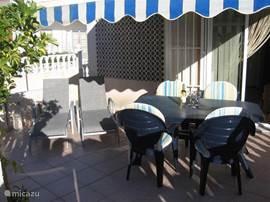 Het terras aansluitend op de woonkamer en keuken met ligstoelen en buitendouche.