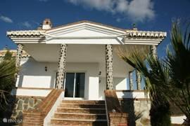 Het terras met de pilaren waar het huis haar naam aan dankt. Het L-vormige terras loopt rondom het huis en is zo'n 35 m2 groot.