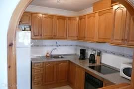 De ruime halfopen keuken is van alle moderne gemakken voorzien om een heerlijke maaltijd te kunnen bereiden.