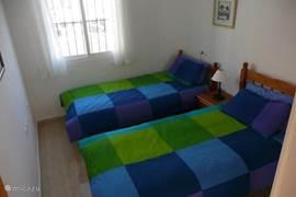 Slaapkamer met 2 1-persoonsbedden, een ventilator en een kledingkast.
