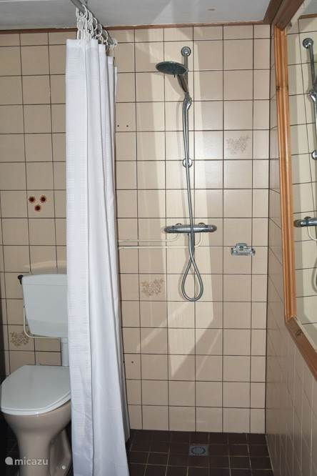 De badkamer is eenvoudig maar heeft wel een thermostaatkraan en regendouche