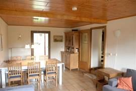 De woonkamer, met grote eettafel. De deur komt uit in de tuin, op de veranda