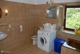 De badkamer op de eerste verdieping. Met onder andere de wasmachine en het toilet