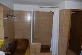 Ligbad en aparte douche in de badkamer