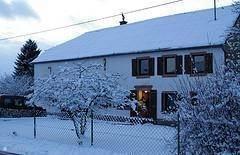 huis in de sneeuw. De voorzijde van het huis, linkerzijde is garage en rechterzijde is woongedeelte.