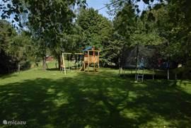 De achtertuin, met speelhuis, glijbaan, schommels en een grote trampoline