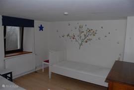 De kinderkamer met 2 eenpersoons bedden. Aan de muur een nachtlampje. Laminaat op de vloer. Deze kamer bevindt zich op de eerste verdieping