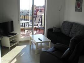 In de woonkamer heeft u veel licht, een bank en een fauteuil. De flatscreen met satelietontvanger met Nederlandse zenders. Door de schuifdeuren komt u op het balkon met een tuinset.