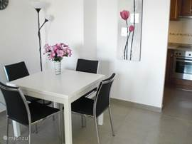 Aan de andere kant van de woonkamer staat de eethoek met vier stoelen.