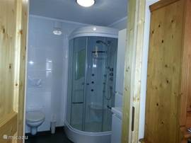 Spacious bathroom with underfloor heating. The bathroom has a toilet, luxury shower and vanity unit.