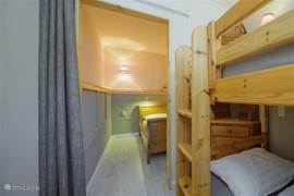"1 of 2 interconnecting bedrooms, the ""nursery"" with bunk beds. There are also two small closets present. The two bedrooms are separated by a curtain from one another."