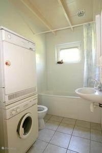 De badkamer is voorzien van wastafel, toilet, ligbad, wasmachine en wasdroger.