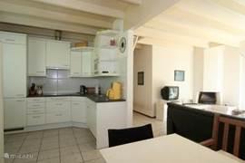 De keuken is voorzien van keramische kookplaat, vaatwasser, magnetron en koelkast met vriezer.