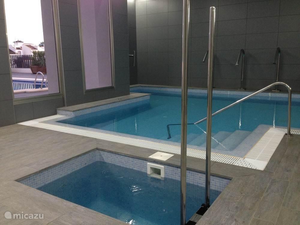 Het gemeenschappelijke binnen zwembad met jacuzzi