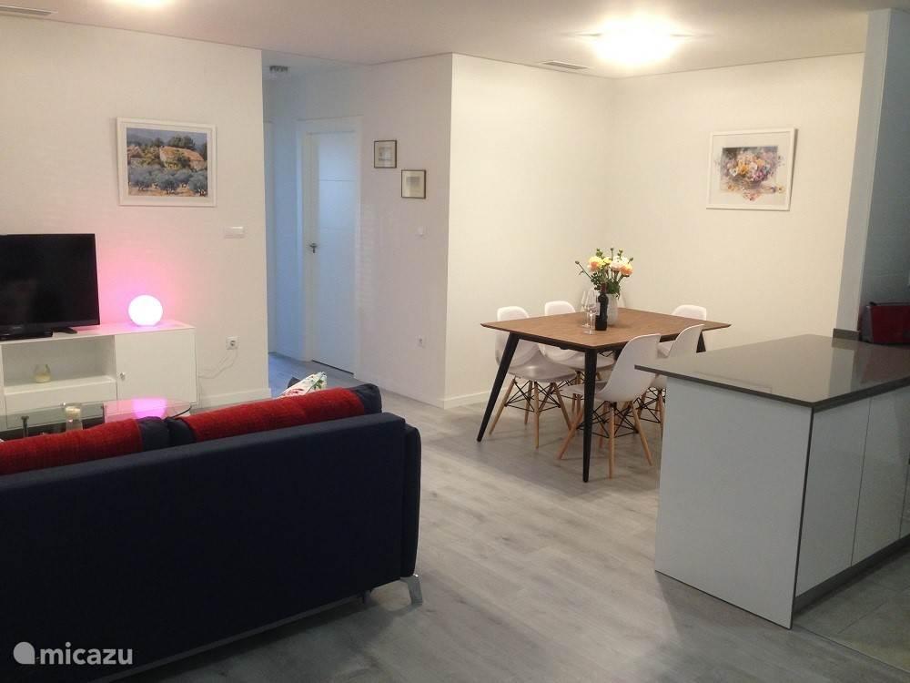 De zitkamer met eethoek, bankstel, salontafel en TV met meubel
