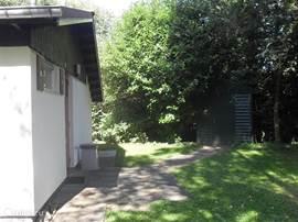 Achter de bungalow staat tussen de bomen een schuurtje voor de fietsen en de tuinmeubelen. De sleutel van de schuur hangt in de hal naast de cv-ketel
