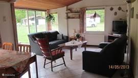 Gezellige woonkamer met bankstel, fauteuil en flatscreen t.v., radio/cd speler en dvd recorder.
