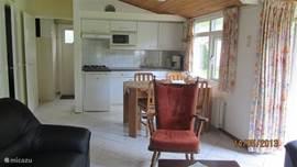 Eethoek bij de open keuken met afzuigkap, magnetron, koelkast en ruim voldoende keukengerei.