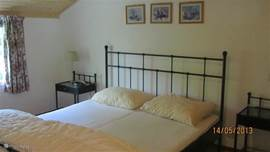 De grootste slaapkamer met o.a. tweepersoonsbed, 2 nachtkastjes, garderobekast en wastafel.